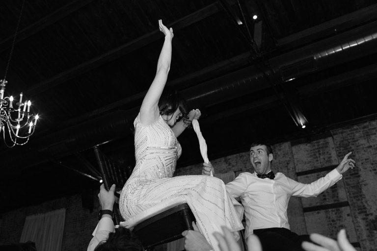 Bride and groom lifted in chairs at their wedding